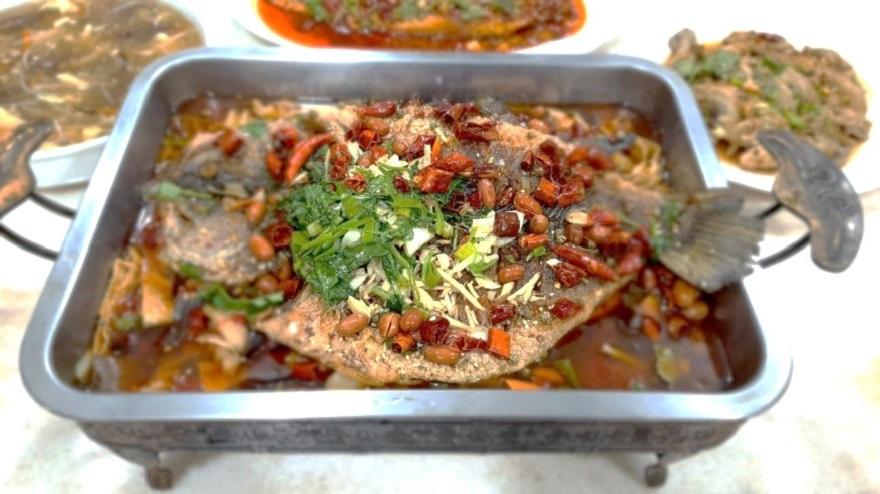 新住民古麗將四川名菜「重慶烤魚」原汁原味在臺呈現,呼應春節年年有餘的好預兆。