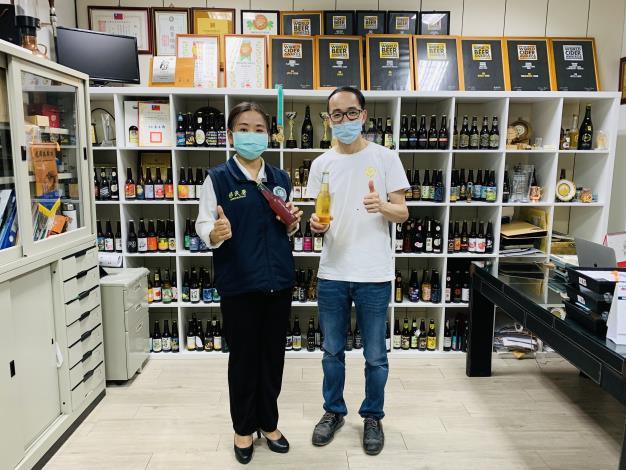 鄧淑達先生(右)向主任黃英貴(左)分享釀造的水果酒.JPG