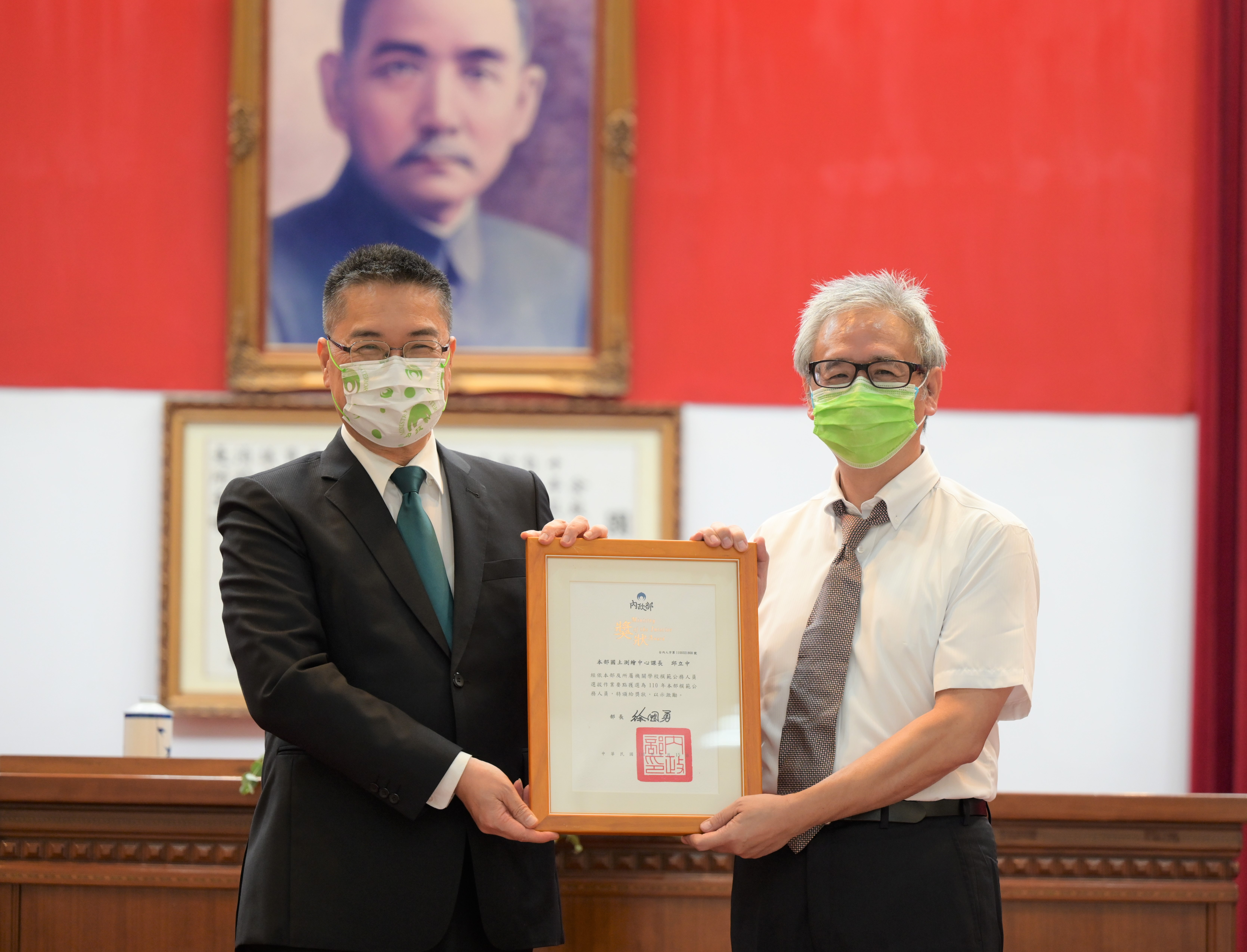 內政部徐部長國勇(左)頒贈模範公務人員獎狀予本中心邱課長立中
