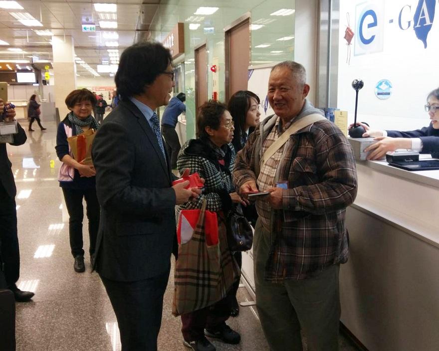 葉俊榮部長於松山機場 e-Gate 註冊櫃檯發放紅包予等待註冊之旅客