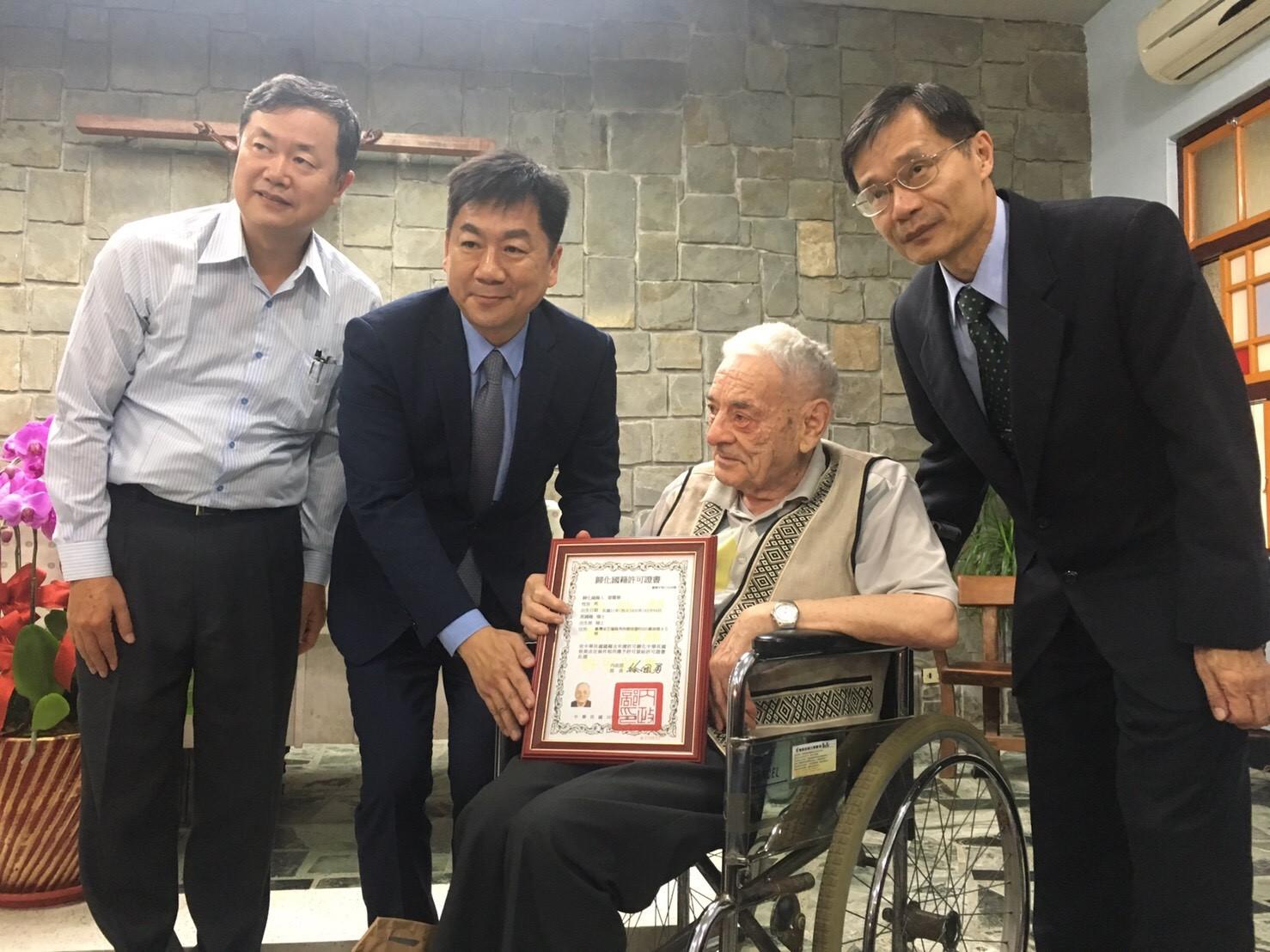 陳政務次長宗彥(左二)親送國籍許可證書給雷神父震華(右二)