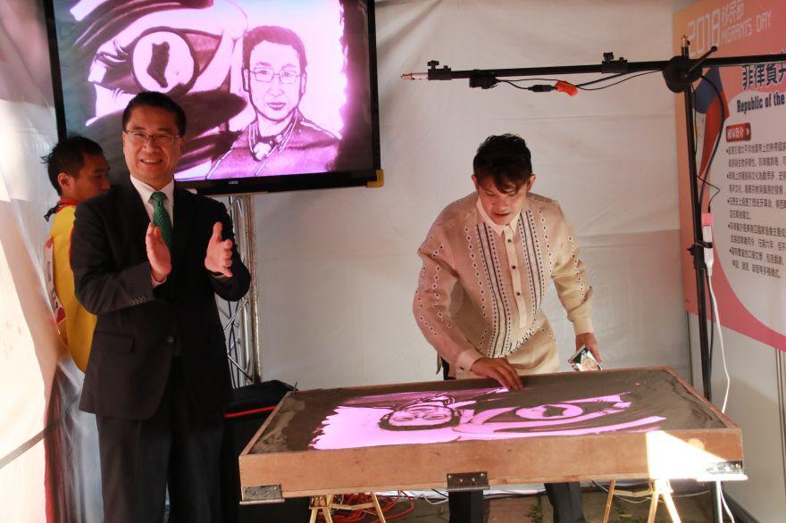 內政部部長徐國勇(左)非常讚賞菲律賓籍藝術家馬力歐(右)沙畫表演