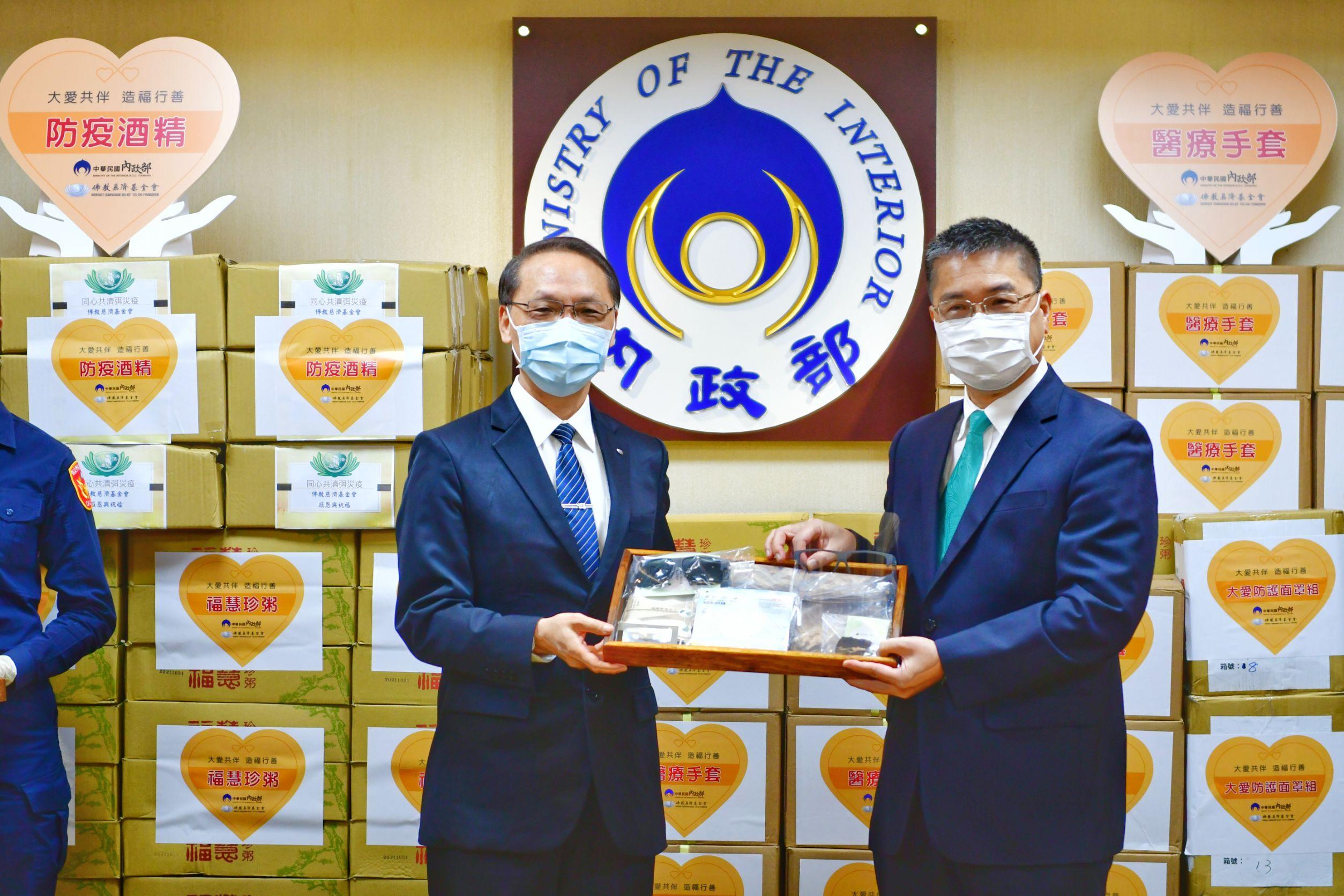 慈濟慈善事業基金會執行長顏博文(左)贈送防護用品予內政部長轉送第一線防疫人員