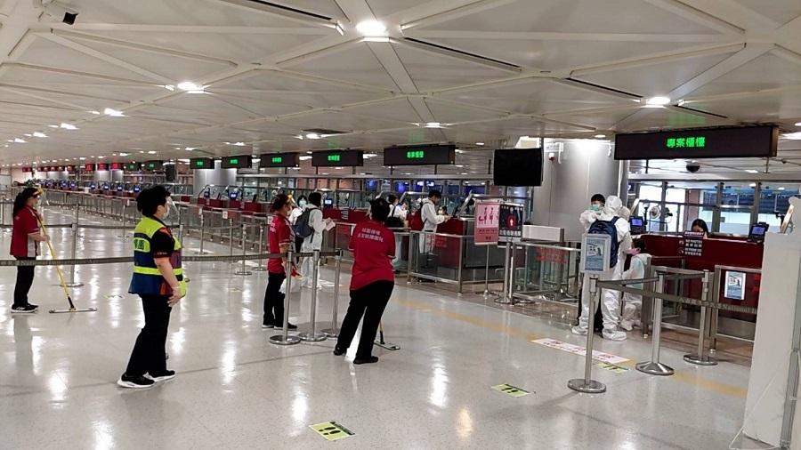 身著防護衣的旅客等待入境查驗通關