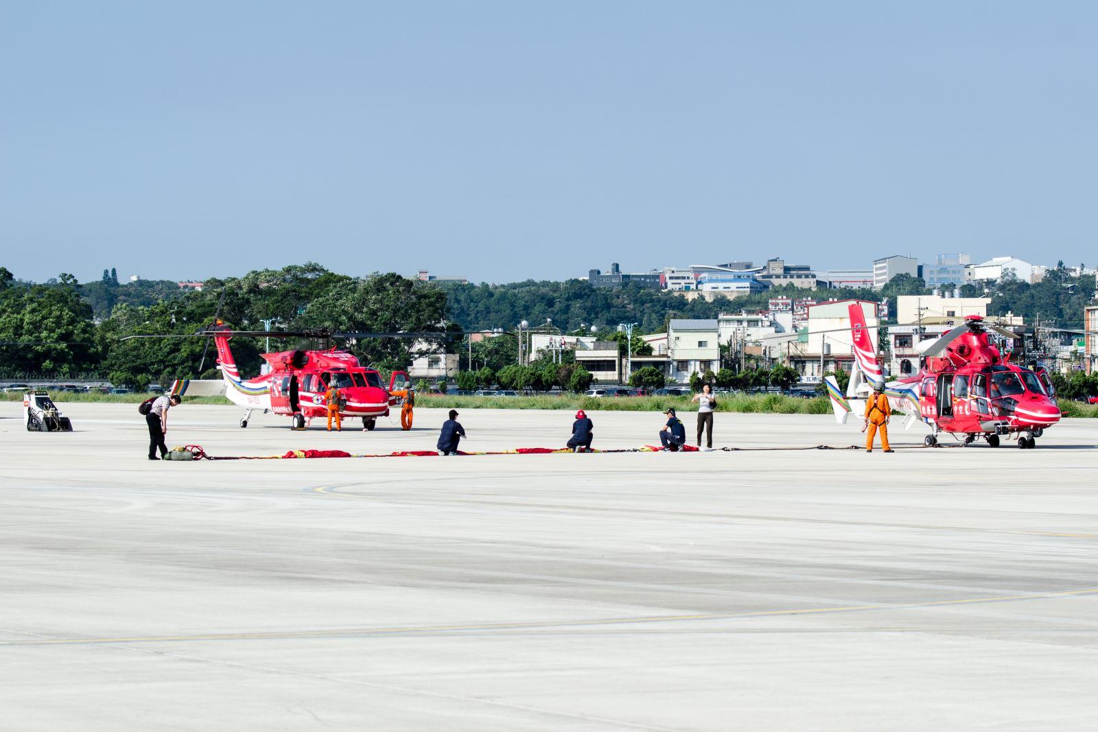 空勤總隊直升機吊掛巨幅國旗及「風雨英雄」旗幟及各式救災設備