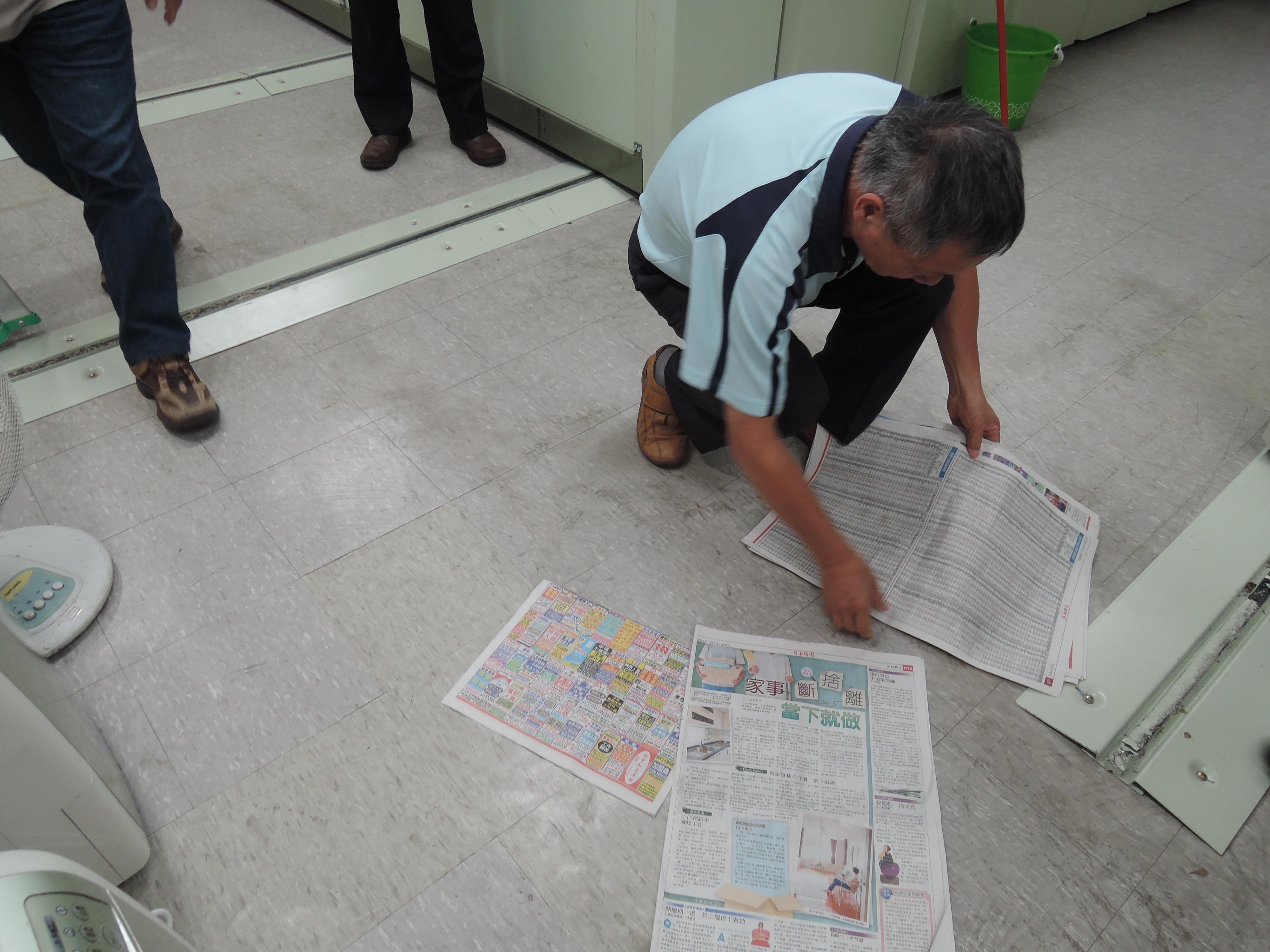 實地演練05-環境控制組於地面鋪設報紙吸水.jpg